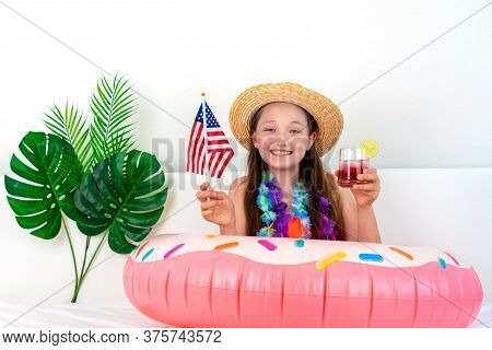 Happy Little Girl Sits On A Bed In A Hat And Holds A Cocktail And An American Flag In Her Hands. Imi