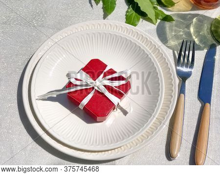 Red Gift Box With White Bow On White Plate Close-up Top View. Engagement, Wedding, Celebrating, Gift