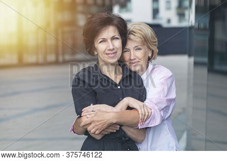 Two Happy Positive Women, Female Friends Standing Outdoors Office After Work. Couple In Love Hugging