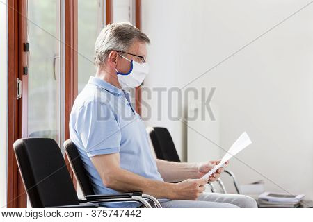 Mature Man In A Bright Waiting Room Of A Hospital Reading The Test Result Of Covid-19