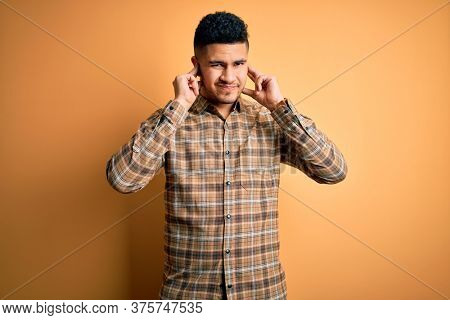 Young handsome man wearing casual shirt standing over isolated yellow background covering ears with fingers with annoyed expression for the noise of loud music. Deaf concept.