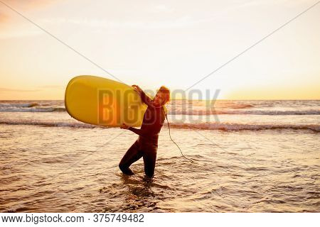 Young Bearded Surfer In Wetsuit With Yellow Surfing Longboard Walk From Water At Sunset Ocean. Water
