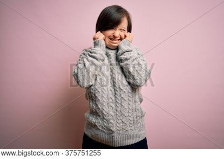 Young down syndrome woman wearing casual sweater over isolated background covering ears with fingers with annoyed expression for the noise of loud music. Deaf concept.