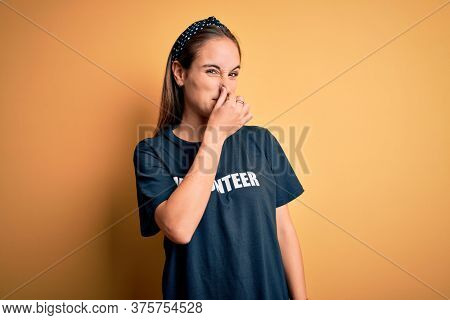 Young beautiful woman wearing volunteer t-shirt doing volunteering over yellow background smelling something stinky and disgusting, intolerable smell, holding breath with fingers on nose. Bad smell