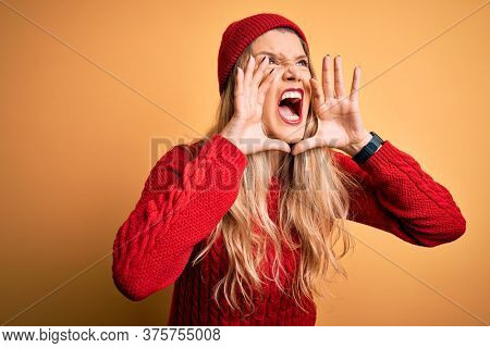 Young beautiful blonde woman wearing casual sweater and wool cap over white background Shouting angry out loud with hands over mouth