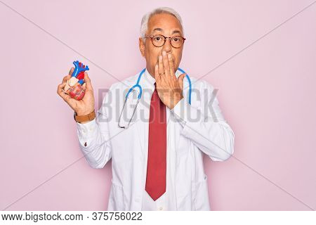 Middle age senior grey-haired cardiologist doctor man holding professional medicine heart cover mouth with hand shocked with shame for mistake, expression of fear, scared in silence, secret concept