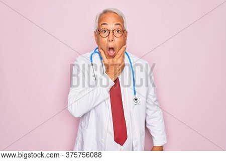 Middle age senior grey-haired doctor man wearing stethoscope and professional medical coat Looking fascinated with disbelief, surprise and amazed expression with hands on chin