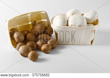 White And Brown Mushrooms Champignons In Wooden Basket On A Light Background. Close Up. Packed Champ