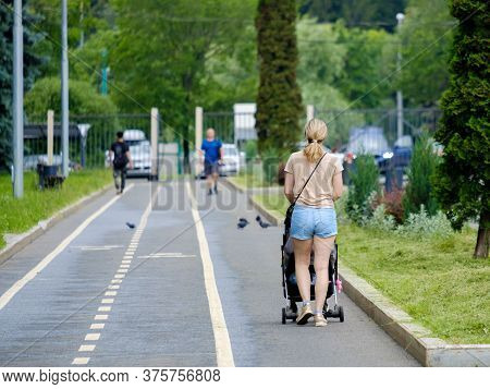 Rear View Of A Young Blonde Woman In Shorts Walking With A Pram. Summer Day In A City Park. Walk Wit