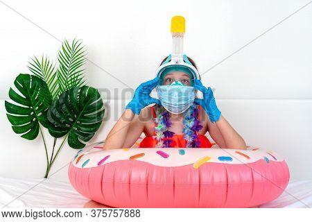 Little Girl In Medical Mask And Gloves Imitates Vacation At Home Quarantine. Domestic Tourism. Coron