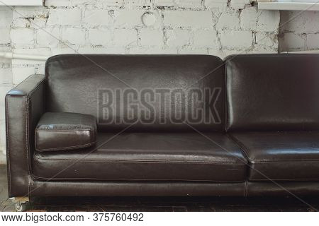 A Large Brown Leather Sofa Stands In A Room With A White Brick Wall