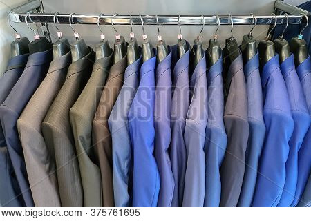Men Row Of Suits On Hanger. Men Clothes Hanging On Wooden Hangers In A Store. Men's Suits On Hanger.