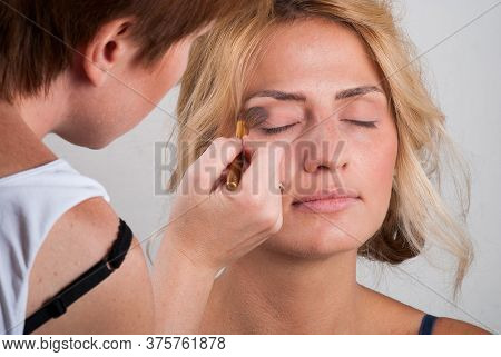 Professional Make-up Artist Doing Makeup To A Blonde Behind The Scenes