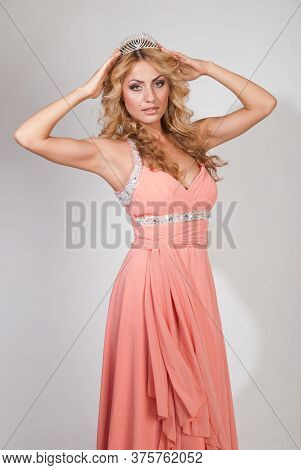 Beautiful Young Woman With Curly Blond Hair And A Crown On Her Head