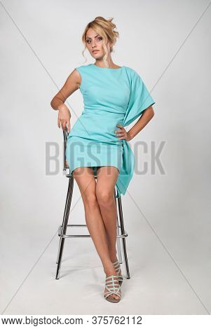 Young Beautiful Woman In A Light Blue Dress Sitting On A Chair