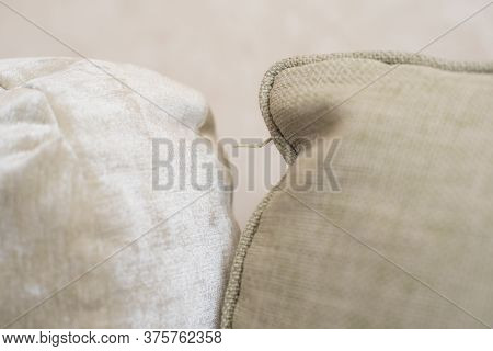 Background Of Two Beautiful Beige Pillows For A Sofa Close-up With Thread On Middle
