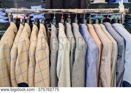 Men Row Of Suits On Hanger. Men Clothes Hanging On Wooden Hangers In A Store. Men's Suits On Hanger.