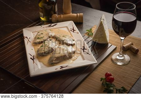 Filet Mignon With Gorgonzola Cheese Sauce, With Red Wine And Green Seasoning On A White Rectangular
