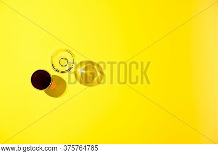 Two Glasses Of Red And White Wine, A Bottle On A Yellow Background. The Concept Of Italian Wine. Pho