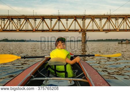 A Boy With His Father Is Kayaking On The River Near The Bridge In The Summer.