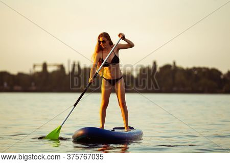Warm Light. Young Attractive Woman Standing On Paddle Board, Sup. Active Life, Sport, Leisure Activi