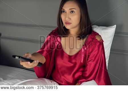 The Woman Is Sleepy While She Is Watching Television In The Bedroom At Night, Asian Girl Wearing Nig