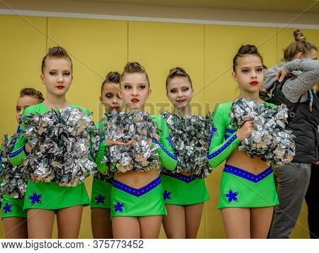 Moscow, Russia - December 22, 2019: Teenage Girls, Athletes In Bright Green Leotards, With Pom-pons