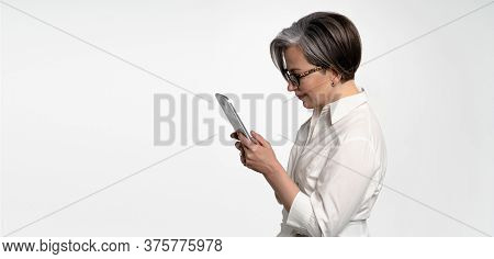 Profile View Of Serious Woman Working With Digital Tablet. Cheerful Mature Business Woman Using Tabl