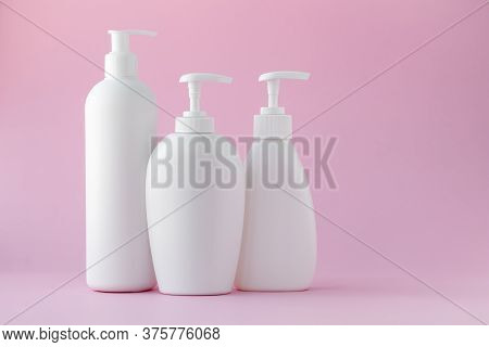 White Plastic Bottles On A Pink Background, A Set Of Cosmetic Containers With A Dispenser. Copy Spac
