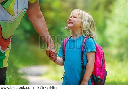 Grandmother Holding Little Girl By Hand While Going To School Or Daycare
