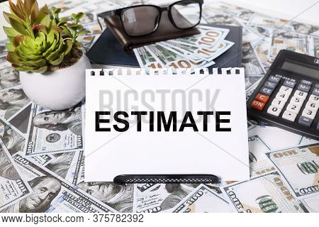 Text Estimate. On A White Background. With Scrolled Money Bills On The Table, Calculator, Glasses, M