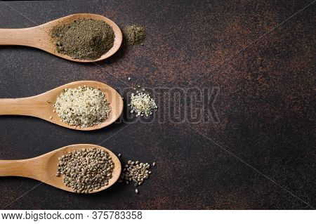 Allowed For Cooking Hemp Seeds, Flour, Kernels In Three Wooden Spoons. View From Above. Copy Space.