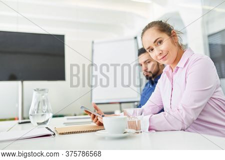 Young business woman as trainee in training in a meeting with a colleague in the office