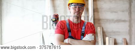 Portrait Of Professional Worker Posing With Crossed Arms In Protective Uniform And Yellow Helmet. Qu