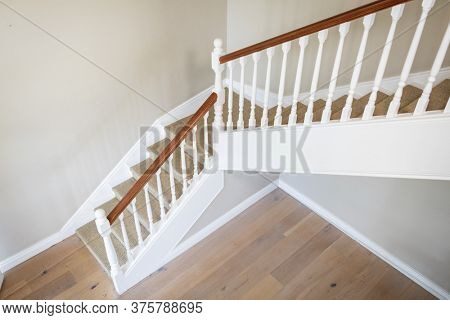 Modern room interior showing big, beautiful white stairs with a wooden handrail and wooden floor with white walls. Luxury apartament interior design.