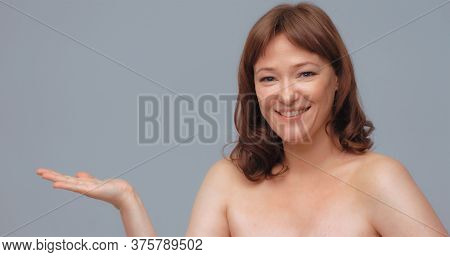 Cherfull Mature Woman Opens Palm Showing Empty Space For Text Or Promotional Items. Smiling Pretty W