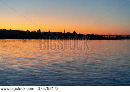 Evening Cityscape And Sunset Over Dnipro. View On Right Bank Of Dnieper River. Dark Silhouettes Of L
