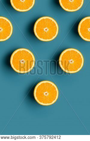 Minimal Pattern Of Oranges Fruit With Pyramid Shape At Blue Background. Concept Of Minimalism Pictur