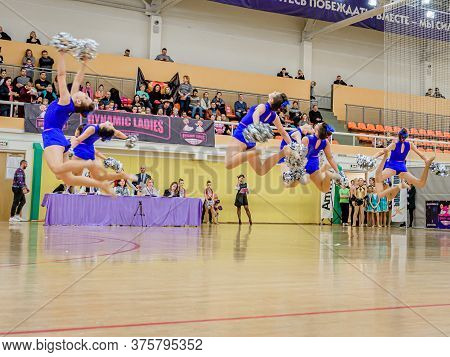 Moscow, Russia - December 22, 2019: Girls With Pom Poms In Blue Sports Uniforms Jump High, Performin