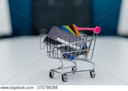 A Mini Shopping Trolley Full Of Credit Cards Stands On A White Table. No People. Close-up Of A Cart