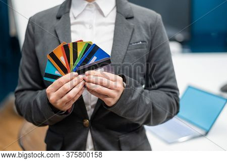 A Faceless Woman In A Suit Holds Several Multi-colored Credit Cards. A Bank Employee Shows A Lot Of