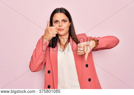 Young beautiful brunette businesswoman wearing elegant jacket over isolated pink background Doing thumbs up and down, disagreement and agreement expression. Crazy conflict