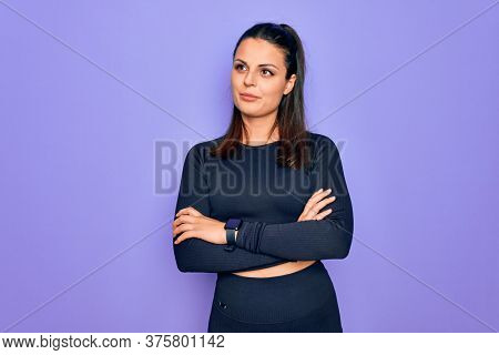 Young beautiful brunette sporty woman wearing casual sportswear over purple background looking to the side with arms crossed convinced and confident