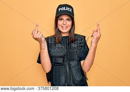 Young beautiful brunette policewoman wearing police uniform bulletproof and cap Showing middle finger doing fuck you bad expression, provocation and rude attitude. Screaming excited
