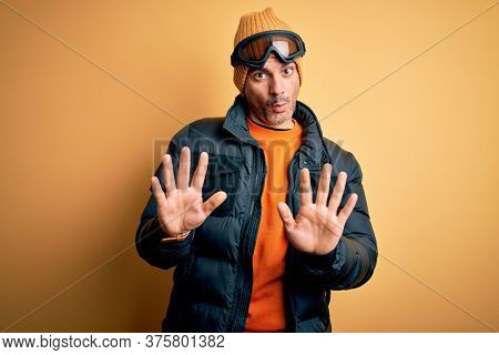 Young handsome skier man skiing wearing snow sportswear using ski goggles Moving away hands palms showing refusal and denial with afraid and disgusting expression. Stop and forbidden.