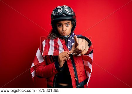African american patriotic motorcyclist girl wearing moto helmet wearing united states flag pointing with finger to the camera and to you, hand sign, positive and confident gesture from the front