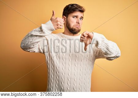 Young blond man with beard and blue eyes wearing white sweater over yellow background Doing thumbs up and down, disagreement and agreement expression. Crazy conflict