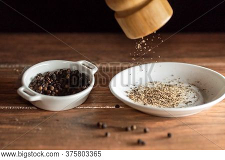Freshly Ground Black Peppercorns And Whole Black Peppercorns On A White Ceramic Plate And Wooden Tab