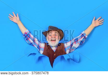 Happy Bearded Man In Cowboy Hat Looking Through Paper. Handsome Cowboy In Plaid Shirt.portrait Of Be