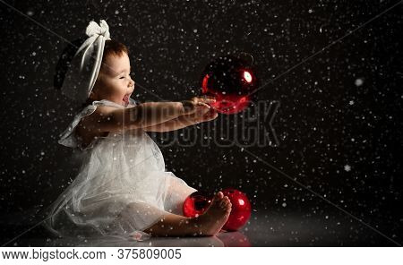 Girl In A White Headband And Barefoot Dress. She Holds Two Red Balls In Front Of Her, Sits On The Fl